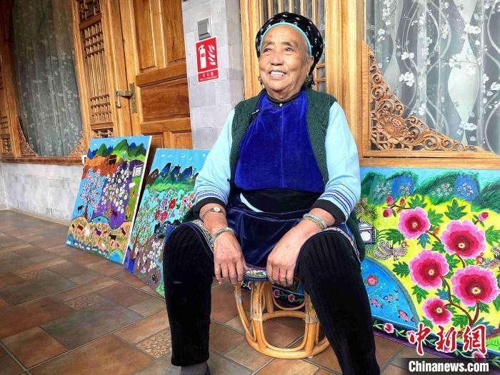 """图为""""农民画家""""王秉秀坐在她的油画作品前。 缪超 摄"""