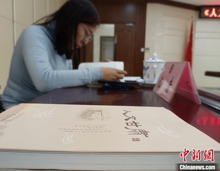 2020年12月中旬,《人文甘肃》出版发行3周年暨读书活动座谈会在兰州召开。图为民众在活动现场阅读《人文甘肃》第7辑。(资料图) 张婧 摄